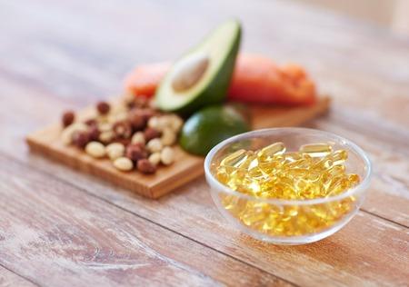 gezonde voeding, dieet en omega-3 voedingssupplementen concept - close-up van koude lever olie capsules in glazen kom en eten op tafel Stockfoto