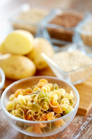 carbohydrate: diet, cooking, culinary and carbohydrate food concept - close up of pasta and other foodstuffs in glass bowls on table Stock Photo