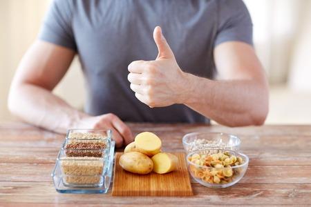 gesunde Ernährung, Diät, Gestik und Menschen Konzept - Nahaufnahme von männlichen Händen Daumen nach oben mit kohlenhydratreiche Lebensmittel auf dem Tisch zeigt
