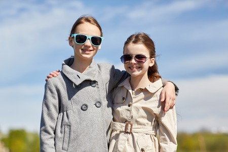 pre teen girls: people, children, friends and friendship concept - happy little girls in sunglasses hugging outdoors Stock Photo