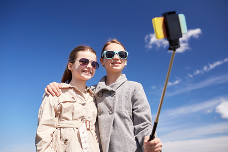 preteen girl: people, children, friends and friendsip concept - happy girls taking picture with smartphone on selfie stick outdoors