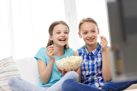 children eating: people, children, television, friends and friendship concept - two happy little girls watching comedy movie on tv and eating popcorn at home Stock Photo