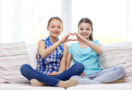 preteens girl: people, children, friends and friendship concept - happy little girls sitting on sofa and showing heart shape hand sign at home Stock Photo