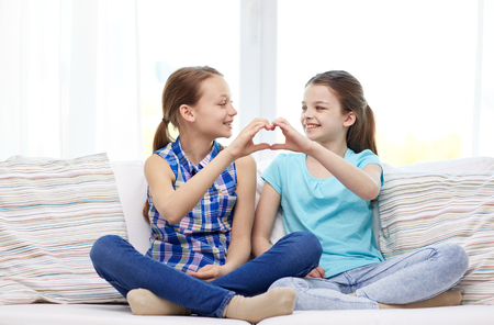 heart hands: people, children, friends and friendship concept - happy little girls sitting on sofa and showing heart shape hand sign at home Stock Photo