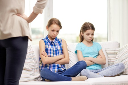 sad little girl: people, children, misbehavior, friends and friendship concept - upset feeling guilty or displeased little girls sitting on sofa and angry mother at home Stock Photo