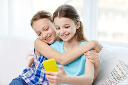 kids hugging: people, children, technology, friends and friendship concept - happy little girls sitting on sofa and taking selfie with smartphone and hugging at home