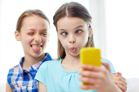 people, children, technology, friends and friendship concept - happy little girls taking selfie with smartphone and having fun at home Imagens