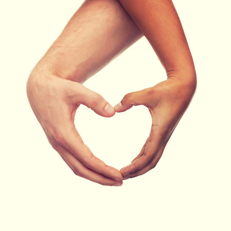 heart in hand: love and relationships concept - closeup of woman and man hands showing heart shape