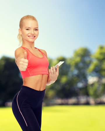 shaping: sport, fitness, technology, internet and healthcare concept - smiling sporty woman with smartphone showing thumbs up