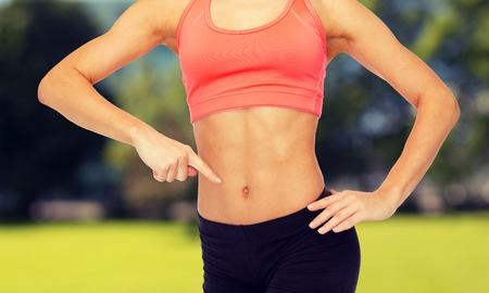 six girls: fitness, exercise and diet concept - close up of woman pointing finger at her six pack Stock Photo
