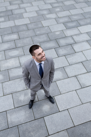 young executive: business, development and people and concept - young smiling businessman outdoors from top