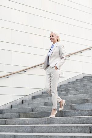bajando escaleras: negocio, la gente y el concepto de la educación - joven empresaria sonriente caminando por las escaleras al aire libre Foto de archivo