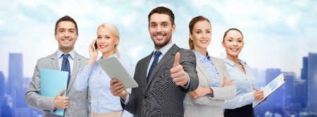 business, people, technology, gesture and office concept - group of smiling businessmen with tablet pc computer showing thumbs up over city background