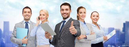 negocio, la gente, la tecnología, el gesto y el concepto de Oficina - grupo de hombres de negocios sonriente con el ordenador de la PC de la tableta muestra los pulgares para arriba sobre el fondo de la ciudad Foto de archivo
