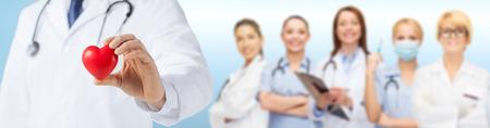 Medizin, Menschen, Nächstenliebe, Gesundheitswesen und Kardiologie Konzept - Nahaufnahme von männlichen Arzt Hand hält rotes Herz über Ärzteteam Standard-Bild