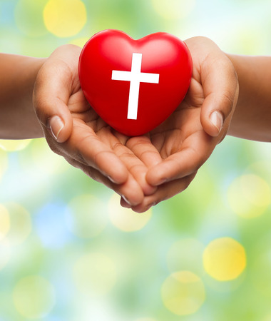people in church: religion, christianity and charity concept - close up of female hands holding red heart with christian cross symbol over green lights background
