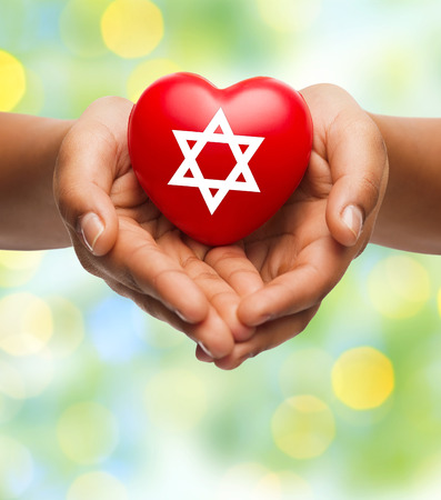 religion, christianity, jewish community and charity concept - close up of female hands holding red heart with star of david symbol over green lights background Stock Photo