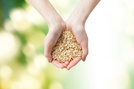 cereals holding hands: healthy eating, dieting, vegetarian food and people concept - close up of woman hands holding oatmeal flakes over green natural background