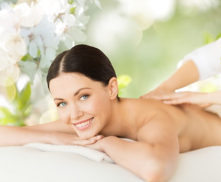 people, beauty, spa and body care concept - happy beautiful woman having back massage over green natural cherry blossom background Stock Photo