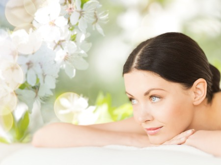 wellness woman: people, beauty, spa and body care concept - happy beautiful woman lying on massage desk over green natural cherry blossom background