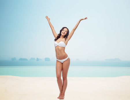 resort beach: people, fashion, swimwear, summer and beach concept - happy young woman posing in white bikini swimsuit dancing with raised hands over infinity pool at beach resort Stock Photo