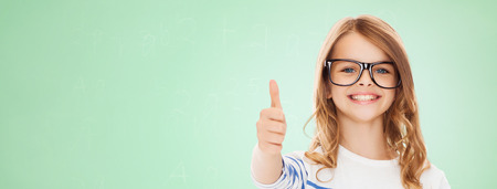 approval: education, school, childhood, people and vision concept - smiling cute little girl with black eyeglasses showing thumbs up gesture over green chalk board background Stock Photo