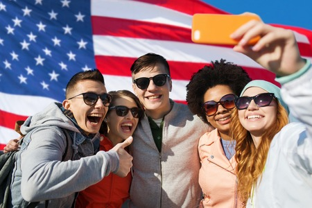 july: people, international friendship and technology concept - group of happy teenage friends taking selfie with smartphone and showing thumbs up over american flag background