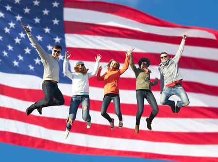 人々、自由、幸福、十代のコンセプト - アメリカ国旗背景飛び越えて高いサングラスで幸せな国際友人のグループ