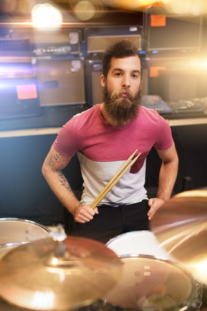 cymbals: music, sale, people, musical instruments and entertainment concept - male musician with drumsticks playing cymbals at music store or concert stage over lights