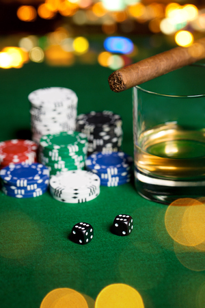 double the chances: gambling, fortune and entertainment concept - close up of casino chips, whisky glass, dice and cigar on green table surface over holidays night lights background Stock Photo