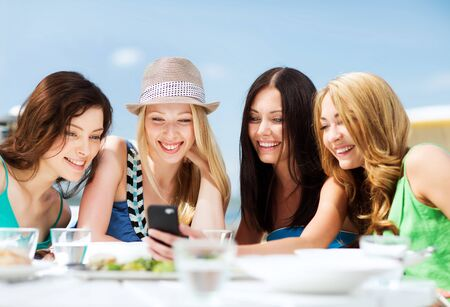 beautiful pictures: summer holidays, vacation and technology - girls looking at smartphone in cafe on the beach