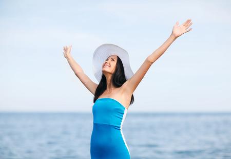 vacanze estive e vacanze - ragazza con le mani in alto sulla spiaggia