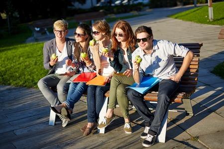 personas comiendo: la educación, la comida, la gente y el concepto de la amistad - grupo de estudiantes felices comiendo manzanas verdes