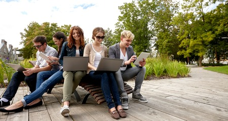 people having fun: summer, communication, technology , education and teenage concept - group of students or teenagers with laptop and tablet pc computers at park or campus