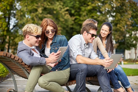 couple outdoor: summer, technology, education and teenage concept - group of happy students or teenagers with tablet pc computer taking selfie
