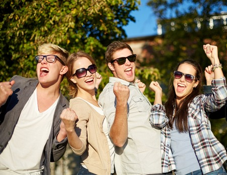 boy beautiful: summer holidays, friendship, achievement and success concept - group of happy friends showing triumph gesture at campus or city park Stock Photo