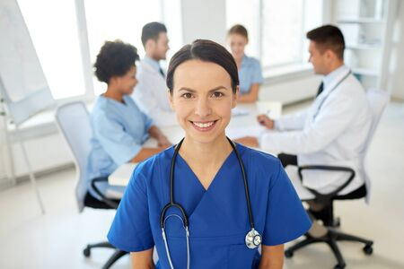 black nurse: health care, profession, people and medicine concept - happy female doctor or nurse over group of medics meeting at hospital Stock Photo