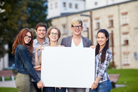 education, campus, friendship and people concept - group of happy teenage students holding big white blank billboard Foto de archivo