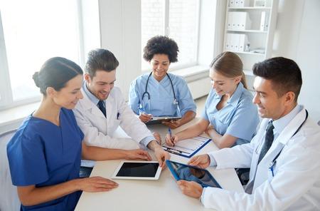 教育: 醫院,醫療教育,醫療衛生,人員和醫學概念 - 一群快樂與醫生在醫療辦公室Tablet PC計算機會議