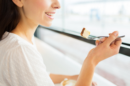 woman eat: food, dessert, people and lifestyle concept - close up of smiling young woman holding fork and eating cake at cafe or home Stock Photo