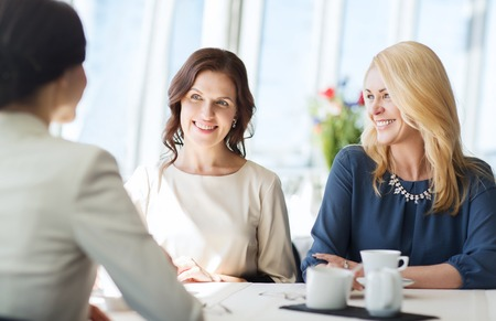 Les gens, la communication et le concept de mode de vie - femmes heureuses de boire du café et parler au restaurant Banque d'images - 53659101