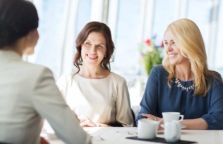 mujeres elegantes: personas, la comunicaci�n y el estilo de vida concepto - mujeres felices beber caf� y hablando en el restaurante Foto de archivo