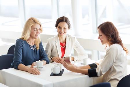 mujeres elegantes: las personas, los días de fiesta, la tecnología y el concepto de estilo de vida - mujer feliz con teléfono inteligente en el restaurante Foto de archivo