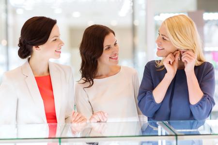 mujeres juntas: la venta, el consumo, las compras y el concepto de la gente - Mujeres felices que eligen y que intentan en los pendientes en el almacén de la joyería