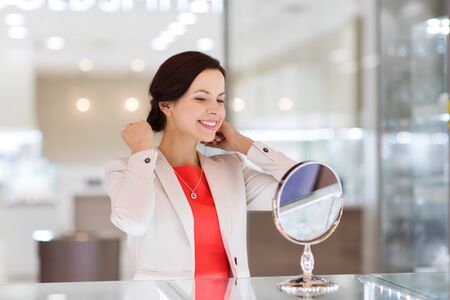jewelry store: sale, consumerism, shopping and people concept - happy woman choosing and trying on pendant at jewelry store Stock Photo