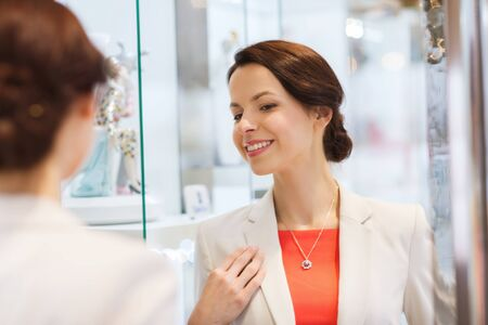 reflection in mirror: sale, consumerism, shopping and people concept - happy woman choosing and trying on pendant at jewelry store Stock Photo