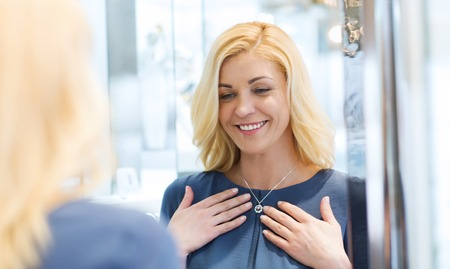 sale, consumerism, shopping and people concept - happy woman choosing and trying on pendant at jewelry store Archivio Fotografico