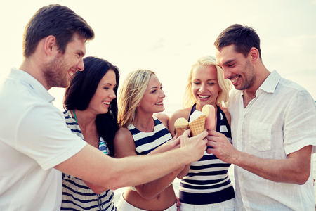 ice cream: summer, holidays, sea, tourism and people concept - group of smiling friends eating ice cream on beach