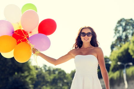 white party: happiness, summer, holidays and people concept - smiling young woman wearing sunglasses with balloons in park