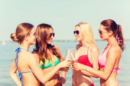 despedida de soltera: las vacaciones de verano, las vacaciones, los viajes y el concepto de la gente - grupo de mujeres jóvenes sonrientes tomando el sol y bebiendo en la playa